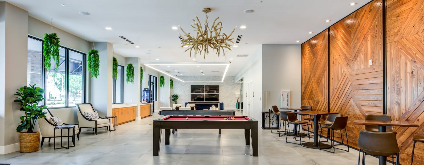 spacious clubroom with ample seating, modern decor & views of surrounding landscaping
